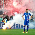 Iceland's Kari Arnason reacts as a steward picks up a flare thrown onto the pitch by Hungary fans after their first goal REUTERS/Yves Herman