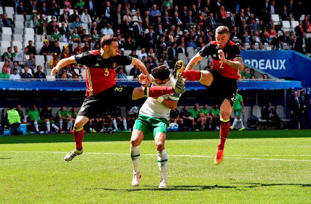 Shane Long gets caught in the crossfire as Belgium's Thomas Vermaelen and Toby Alderweireld lead with their studs up in the air. Photo: Sportsfile