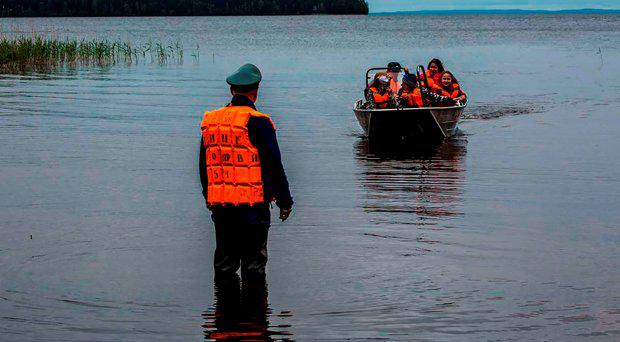 Emergency officers carry surviving children in a boat on Lake Syamozero in Russia's autonomic republic of Korelia on June 19, 2016.