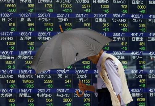 A pedestrian holding an umbrella walks past a stock quotation board outside a brokerage in Tokyo, Japan. REUTERS/Issei Kato