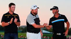 Amateur Jon Rahm of Spain, Shane Lowry of Ireland and Scott Piercy of the United States shake hands on the 18th green following the final round of the U.S. Open at Oakmont
