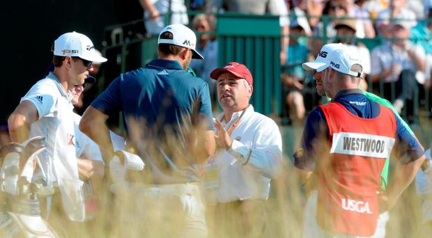 Dustin Johnson (second from left) takes with a rules official on the 12th tee box during the final round of the U.S. Open golf tournament at Oakmont Country Club. Mandatory Credit: Michael Madrid-USA TODAY Sports