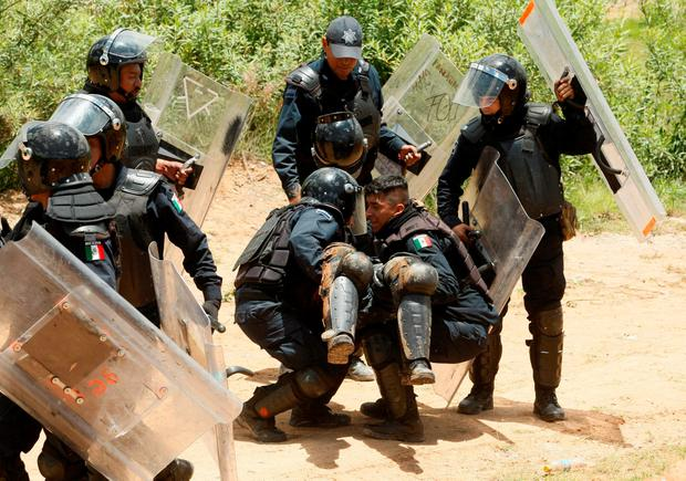 Riot police officers help an injured colleague during clashes with protesters from the National Coordination of Education Workers (CNTE) teachers' union during a protest against President Enrique Pena Nieto's education reform, in the town of Nochixtlan, northwest of the state capital, Oaxaca City, Mexico June 19, 2016