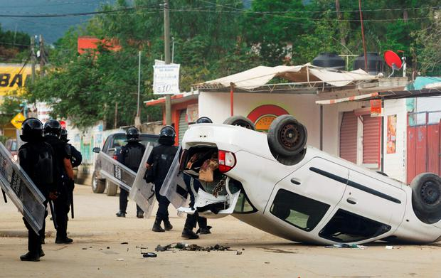 Riot police officers stand guard beside a damaged car after they clashed with protesters from the National Coordination of Education Workers (CNTE) teachers' union during a protest against President Enrique Pena Nieto's education reform, in the town of Nochixtlan, northwest of the state capital, Oaxaca City, Mexico June 19, 2016