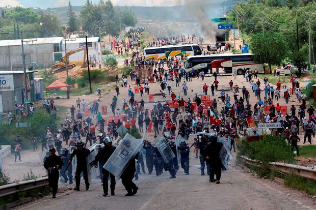 Riot police are forced to fall back as they battle with protesting teachers who were blocking a federal highway in the state of Oaxaca, near the town of Nochixtlan, Mexico, Sunday, June 19, 2016
