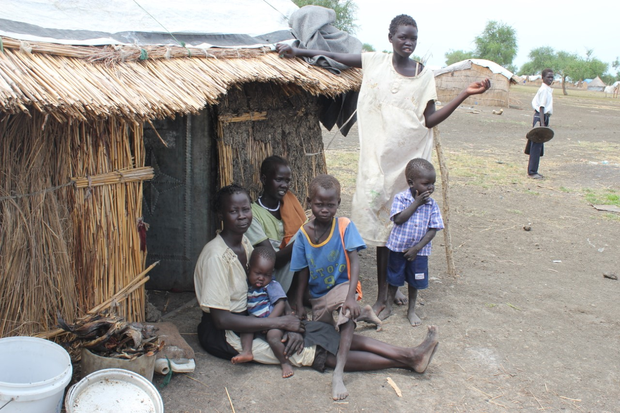 Aweuk and her family outside her thatched hut in Kordor IDP Camp, Melut, South Sudan