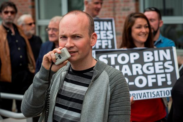 Simon Coveney presence at Council meeting attracts activists demonstrating against the bin charges. Paul Murphy TD with megaphone. Photo: Doug O'Connor