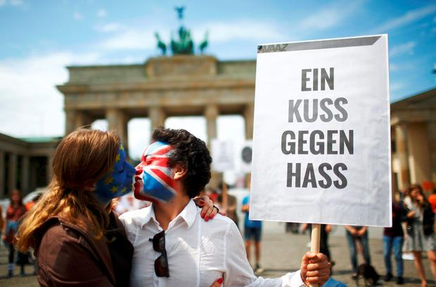 Two activists with the EU flag and Union Jack painted on their faces kiss each other in front of Brandenburg Gate to protest against British exit from the European Union, in Berlin, Germany, June 19, 2016. The sign reads,