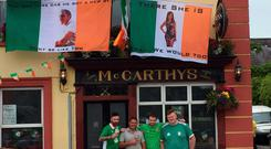 Daniel Hegarty, Tom Fitzgibbon, Darren McNamara and Aaron Ryan stand under their famous flags which are hanging on McCarthy's Bar, Buttevant