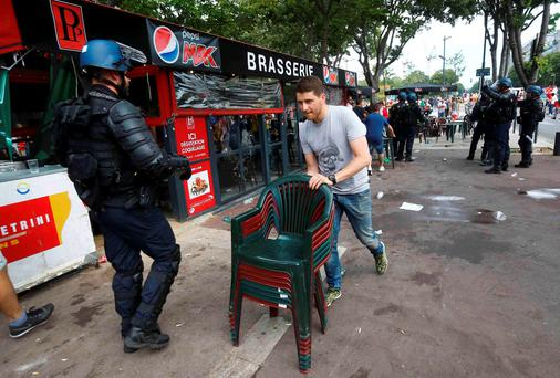 A cafe owner removes chairs during clashes between rival groups of Polish fans in Marseille, France. REUTERS/Wolfgang Rattay
