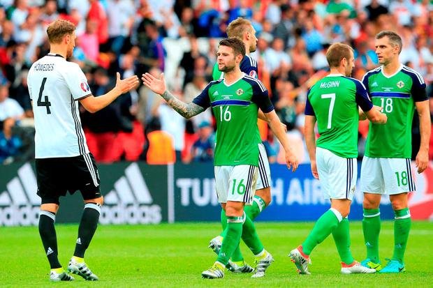 Germany's Benedikt Howedes (left) shakes has with Northern Ireland's Oliver Norwood (centre) after the final whistle