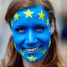 A campaigner against Brexit poses with the EU flag painted on her face, at the Brandenburg Gate in Berlin. Photo: Hannibal Hanschke/Reuters