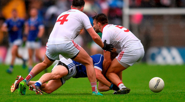 Seanie Johnston of Cavan is tackled by Tyrone's Cathal McCarron, left, and Tiernan McCann during last Sunday's draw – Ulster has opted to wait until Sunday week for the replay, causing disruption to the qualifiers. Photo: Sportsfile