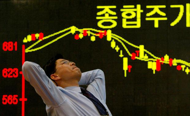 A South Korean employee of a securities firm reacts in front of a graph showing stock price in Seoul