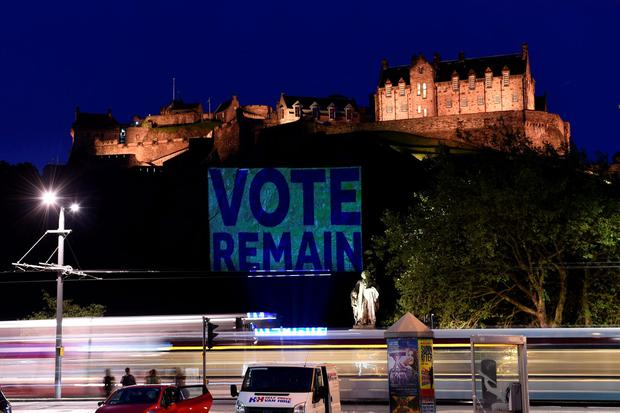 Edinburgh Castle rock is illuminated with a sign to
