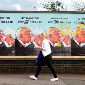 A woman walking past EU referendum posters - by the pro-Remain group, We Are Europe - depicting Donald Trump kissing Brexit advocate Boris Johnson, in Finsbury Park, London. Yui Mok/PA Wire