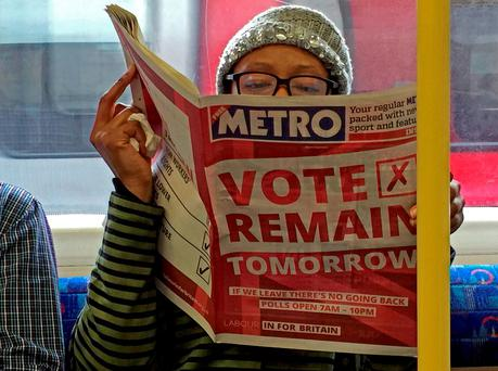 A woman reads a newspaper on the underground in London with a 'vote remain' advert for the BREXIT referendum, Britain June 22, 2016. REUTERS/Russell Boyce