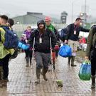 Festival-goers arrive for the Glastonbury Festival at the Worthy Farm site, Somerset, where heavy rain over a prolonged period has caused isolated flooding and muddy fields. Photo: Ben Birchall/PA Wire