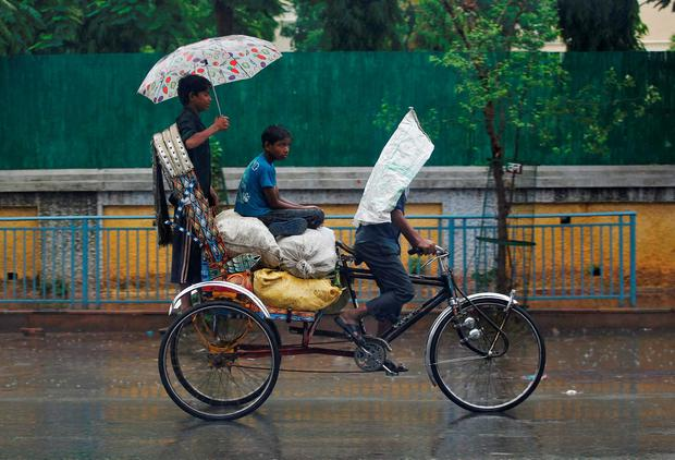 Boys shelter from rain as they travel on a cycle rickshaw in Allahabad, India, June 22, 2016. REUTERS/Jitendra Prakash