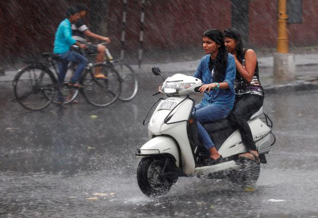People commute during a heavy rain shower in Chandigarh, India, June 22, 2016. REUTERS/Ajay Verma