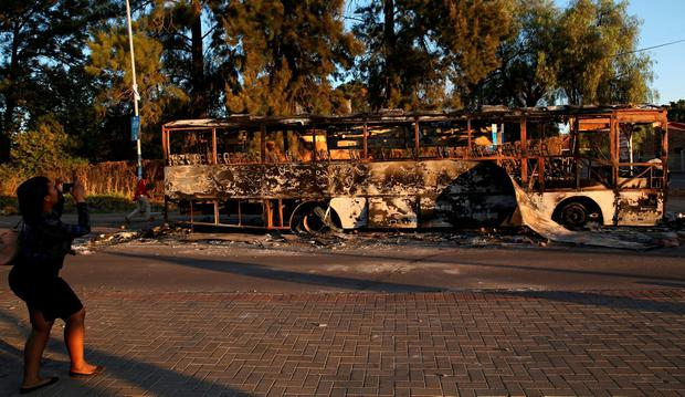A women uses a cellphone to photograph the remains of a burnt out bus used to barricade roads by protesters in Atteridgeville a township located to the west of Pretoria, South Africa June 21, 2016. REUTERS/Siphiwe Sibeko