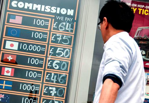 A man looks at a board showing currency exchange rates outside a Bureau de Change in North London, as holidaymakers heading abroad this summer have been flocking to snap up their travel money ahead of tomorrow's EU Referendum. Photo: PA