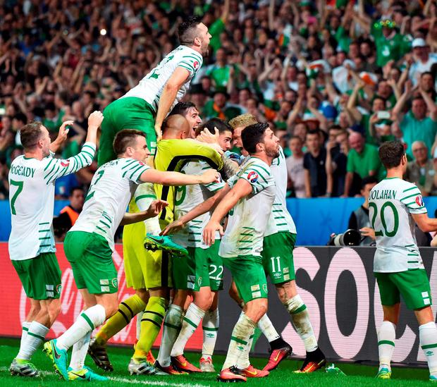 Robbie Brady is mobbed by his Ireland team-mates after scoring the crucial goal in last night's Group E clash in Lille last night. Photo: Philippe Huguen/AFP/Getty Images