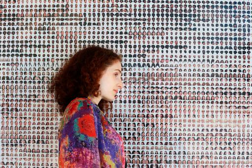 Student Eva O'Brien pictured at the Science Gallery in Trinity College Dublin beside a piece entitled Ground Truth, which uses images of different people's faces as a way of teaching robots to recognise people. Photo: Leon Farrell/Photocall