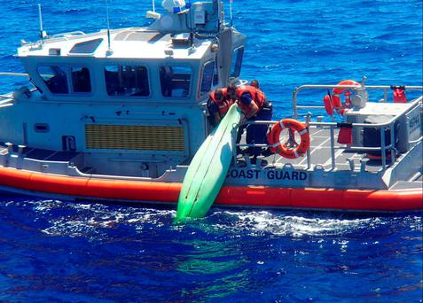 A United States Coast Guard patrol boat crew lifts a kayak found among debris near Sanibel, Florida during a search for a family that went missing on their sailboat, in a picture released by the USCG on June 22, 2016. USCG/Handout via REUTERS