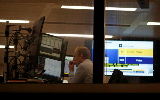 A trader works at his desk as votes are counted for the EU referendum, in London, Britain June 24, 2016. REUTERS/Peter Nicholls