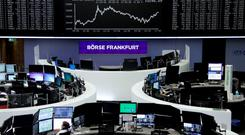 Traders work at their desks in front of the German share price index, DAX board, at the stock exchange in Frankfurt, Germany, June 23, 2016. REUTERS/Staff/Remote