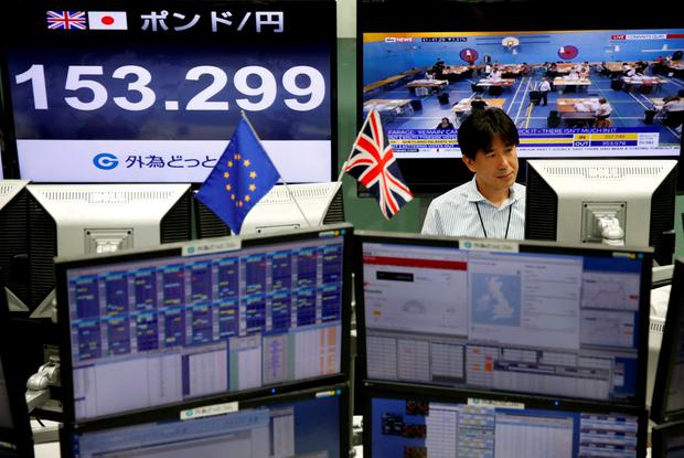 An employees of a foreign exchange trading company works in front of monitors displaying television news on Britain's EU referendum and the Japanese yen's exchange rate against British pound (L) in Tokyo, Japan, June 24, 2016. REUTERS/Issei Kato