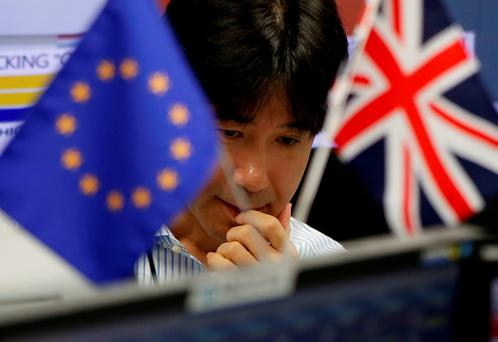 An employees of a foreign exchange trading company works as he is seen between British Union flag and an EU flag in Tokyo, Japan, June 24, 2016. REUTERS/Issei Kato