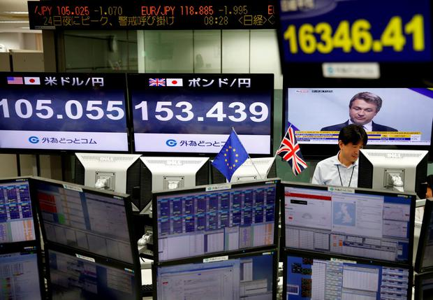 An employees of a foreign exchange trading company works next to monitors displaying television news on Britain's EU referendum, Japan's Nikkei share average (top R), the Japanese yen's exchange rate against British pound (C) and the U.S. dollar (L) in Tokyo, Japan, June 24, 2016. REUTERS/Issei Kato