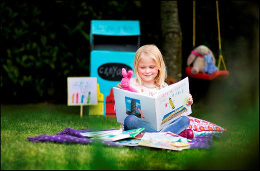 Isobel Conachy (6) enjoying her new book 'The Day The Cayons Come Home'. Photo: David Conachy.