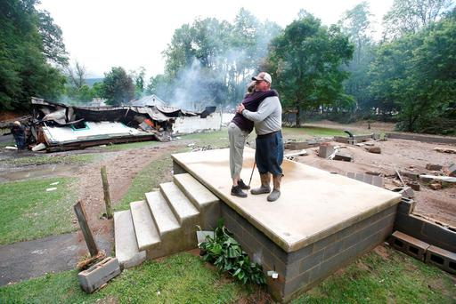 Jimmy Scott gets a hug from Anna May Watson, left, as they clean up from severe flooding in White Sulphur Springs, W. Va. (AP Photo/Steve Helber)