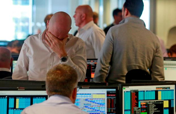 Worry on the faces of traders in London's financial district in a 'truly unprecedented' day of destruction on the world's markets. REUTERS/Russell Boyce