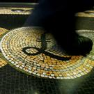 An employee is seen walking over a mosaic of pound sterling symbols set in the floor of the front hall of the Bank of England in London