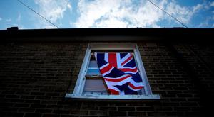 A British flag flutters in front of a window in London, Britain, June 24, 2016 after Britain voted to leave the European Union