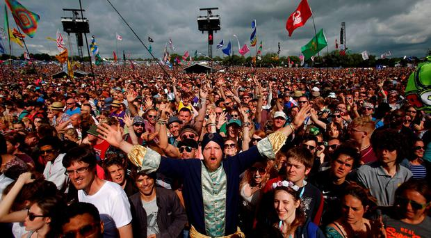 Revellers entertain themselves before the start of the performance of the British band Madness on The Pyramid stage at Worthy Farm in Somerset during the Glastonbury Festival, Britain, June 25, 2016. REUTERS/Stoyan Nenov