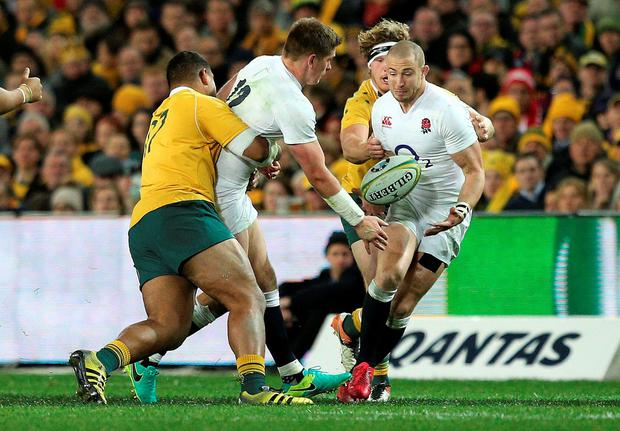 England's Owen Farrell, second left, passes the ball to Mike Brown, right, as Australia's Tevita Kuridrani, left, tackles him during their rugby test match in Sydney. Photo: Rob Griffith/AP Photo