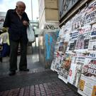 Shockwaves: A man browses through newspapers at a kiosk in Athens yesterday — Britain and the EU haven't even begun divorce talks but they are already bickering, as political and economic repercussions spread around the world. Photo: AP