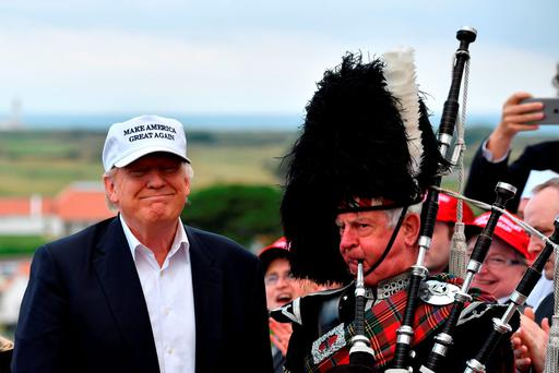 Pipe down: A bagpipe player in full dress stands next to presumptive Republican nominee Donald Trump as he arrives at Trump Turnberry Resort in Scotland last week to officially reopen his golf resort. Photo: Getty