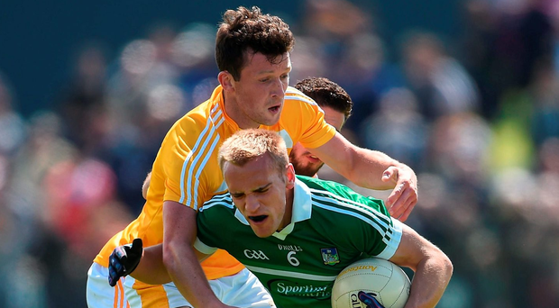 Limerick's Sean O'Dea is tackled by Antrim's Dermott McAleese. Photo: Ramsey Cardy/Sportsfile