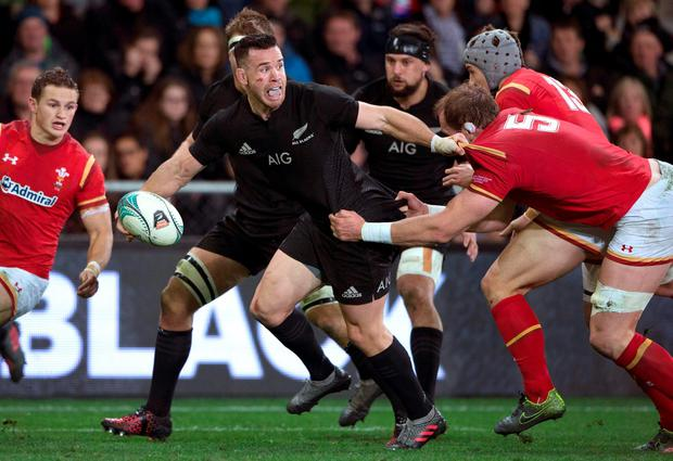 New Zealand All Blacks' Ryan Crotty fends off a tackle. Photo: Brett Phibbs/New Zealand Herald via AP