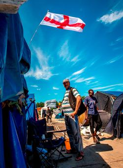nowhere to go: Men stand next to an English flag in the 'Jungle' camp for migrants and refugees in Calais after Britain voted to leave the European Union. Photo: AFP/Getty Images