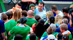 Ireland's John O'Shea holds his son Alfie as he goes over to the fans after the round of 16 match at the Stade de Lyon