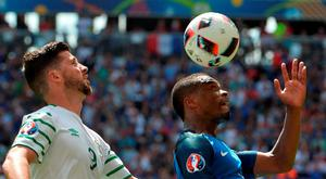 Shane Long of Republic of Ireland challenges Patrice Evra of France during the UEFA Euro 2016 Round of 16 match between France and Republic of Ireland at Stade des Lumieres in Lyon