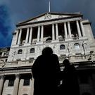 City workers walk past the Bank of England in London. Photo: Toby Melville/Reuters