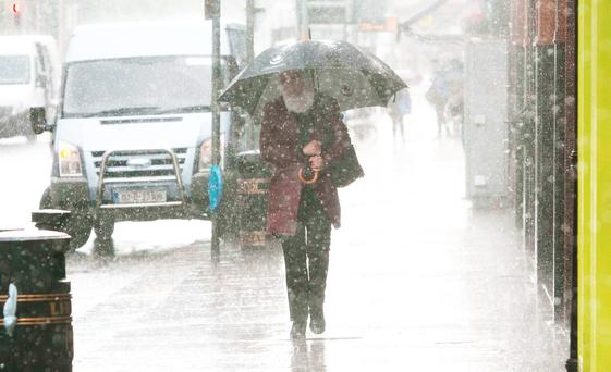Members of the public brave the bad weather in Dublin's city centre. Photo: Gareth Chaney Collins